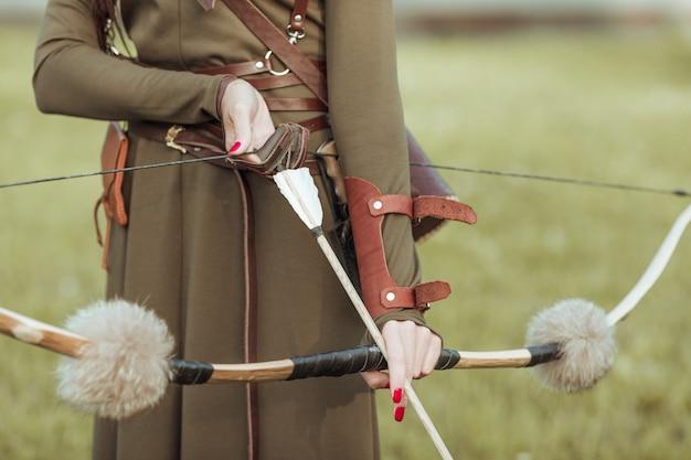 Jonge vrouw krijger met een boog trekt de pees met een pijl, close-up