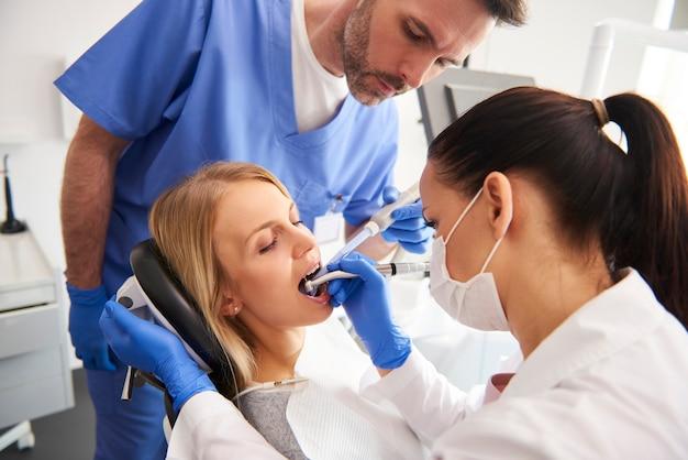Jonge vrouw krijgt behandeling in het kantoor van de tandarts