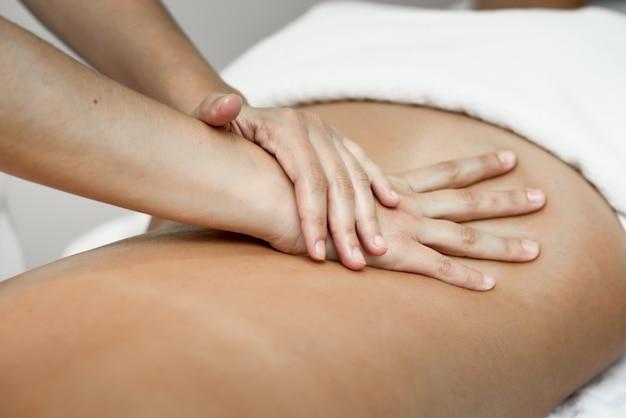 Jonge vrouw krijgt een rugmassage in een spa-centrum.