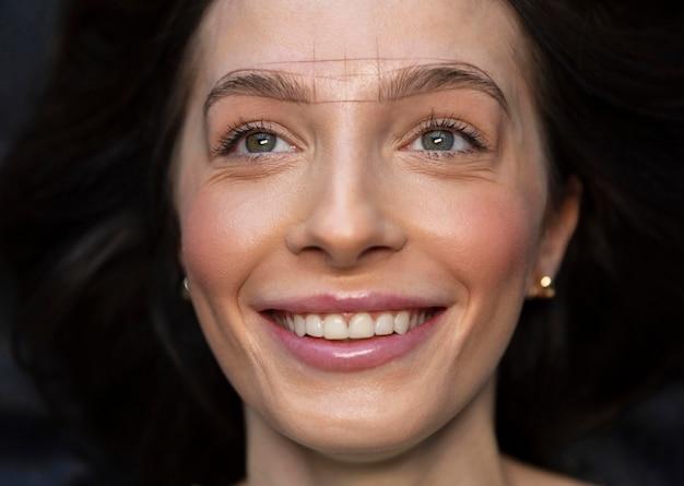 Jonge vrouw krijgt een schoonheidsbehandeling voor haar wenkbrauwen