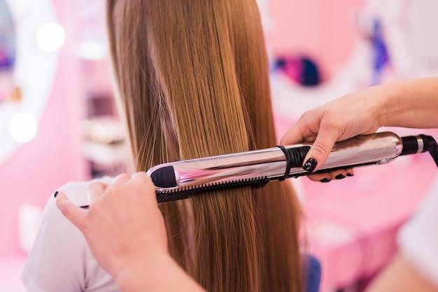 Jonge vrouw krijgt haar haar gekruld door stylist bij salon. mooie jonge kapper die nieuw kapsel geeft aan wijfje in salon