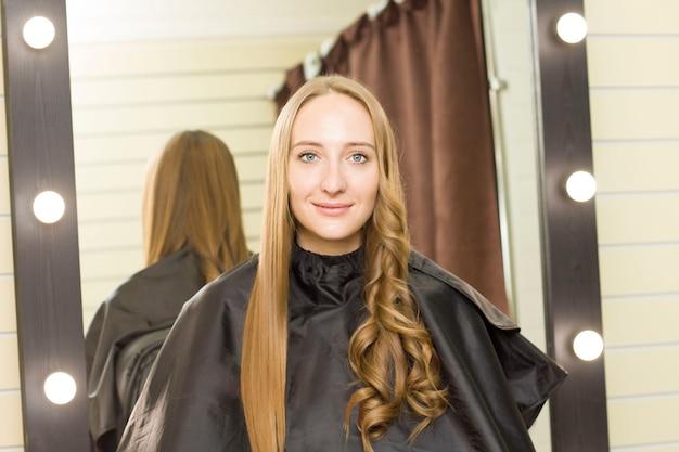 Jonge vrouw krijgt haar haren gedaan in een schoonheidssalon