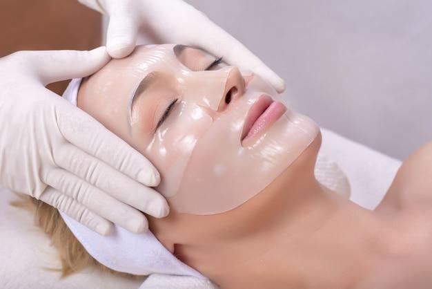 Jonge vrouw krijgt huidmaskerbehandeling op haar gezicht met massagehandschoen