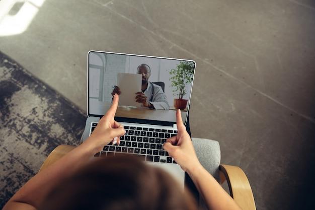 Jonge vrouw krijgt online medische hulp en advies tijdens een videogesprek met een arts die de symptomen controleert en de recepten van het medicijn uitlegt. verbinding tijdens zelfisolatie met laptop, koptelefoon, telefoon.