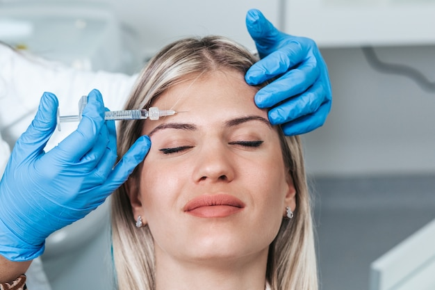 Jonge vrouw krijgt verjongende gezichtsinjecties. de deskundige schoonheidsspecialiste vult vrouwelijke rimpels op met hyaluronzuur.