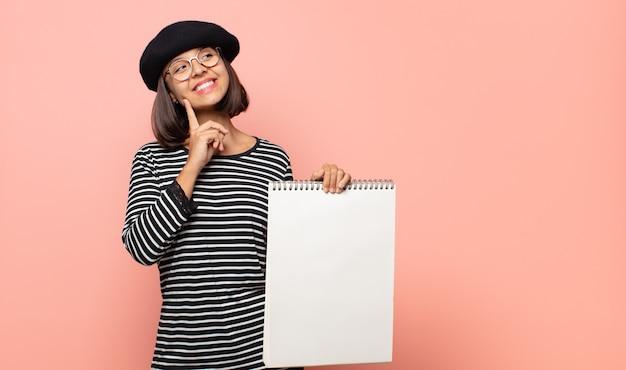 Jonge vrouw kunstenaar gelukkig glimlachen en dagdromen of twijfelen, op zoek naar de kant