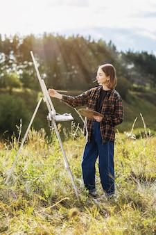 Jonge vrouw kunstenaar schildert een beeld in het park op een zonnige zomeravond