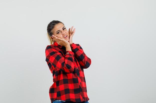 Jonge vrouw kussen gezicht op haar handen in geruit overhemd en op zoek schattig, vooraanzicht.