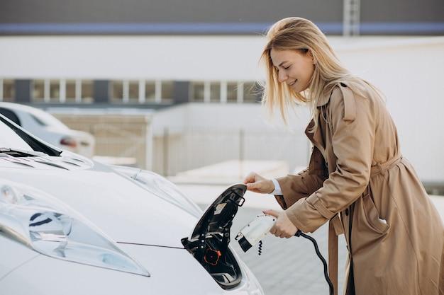 Jonge vrouw laadt haar elektrische auto op met laadpistool