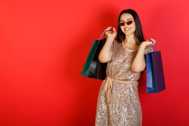 Jonge vrouw lachen in rode zonnebril en jurk met boodschappentassen poseren op rode achtergrond.