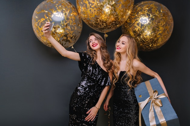 Jonge vrouw lachen met krullend kapsel poseren met plezier tijdens feestje. betoverend feestvarken in zwarte outfit met grote geschenkdoos terwijl haar vriend selfie maakt.