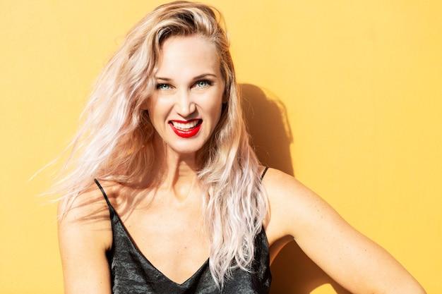 Jonge vrouw lachen op een gele muur
