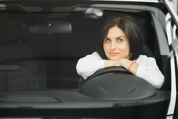 Jonge vrouw lachend in haar nieuwe auto in een showroom