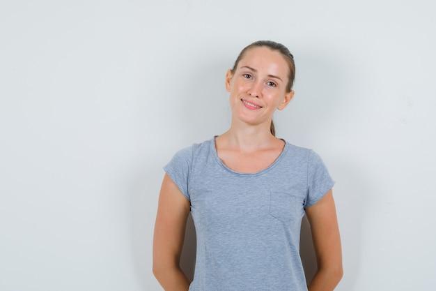 Jonge vrouw lachend met handen op rug in grijs t-shirt, vooraanzicht.