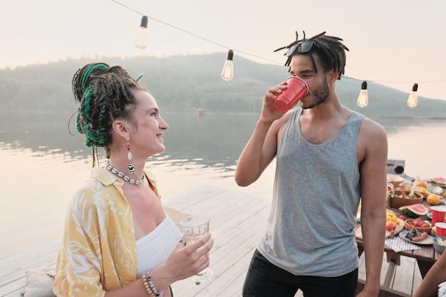 Jonge vrouw lachend naar jonge man terwijl ze buiten op een pier staan en cocktails drinken