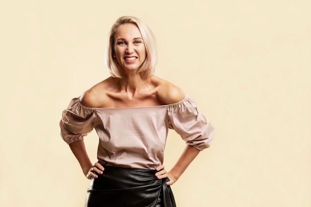 Jonge vrouw lacht. een mooie blondine in een roze trui en een zwart leren rok. gele achtergrond. ruimte voor tekst.