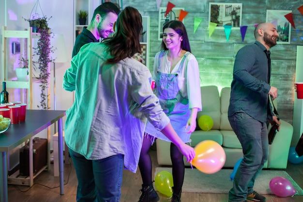 Jonge vrouw lacht op een feestje met haar vrienden en danst op funky muziek.