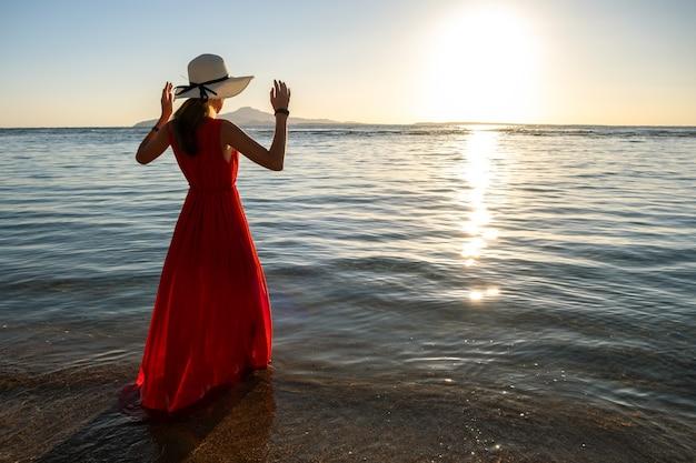 Jonge vrouw lange rode kleding dragen en strohoed die zich in zeewater bevinden bij het strand die van mening van het toenemen zon in de vroege zomerochtend genieten.