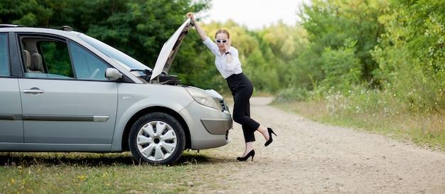 Jonge vrouw langs de weg nadat haar auto kapot is gegaan. ze deed de motorkap open om de schade te zien