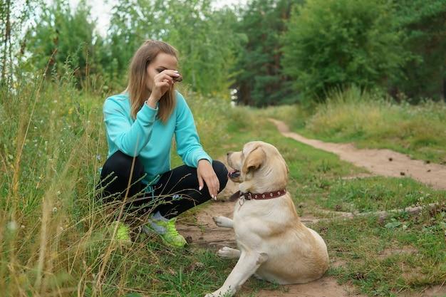 Jonge vrouw leert de instructie van haar grote mooie hond die delicatesse in haar hand houdt terwijl ze door het bos loopt