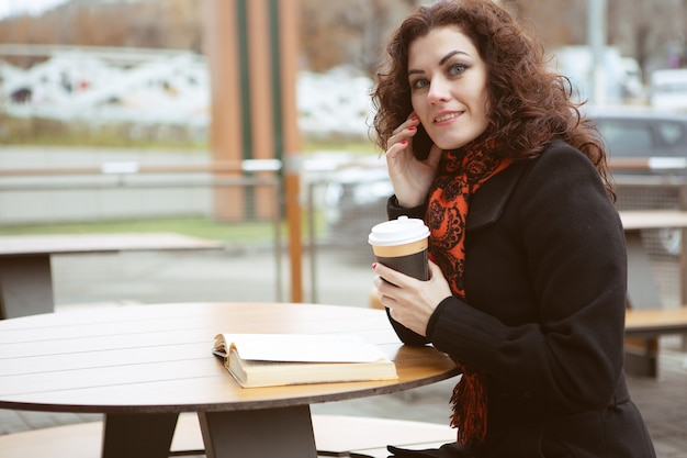 Jonge vrouw leesboek in een straat café