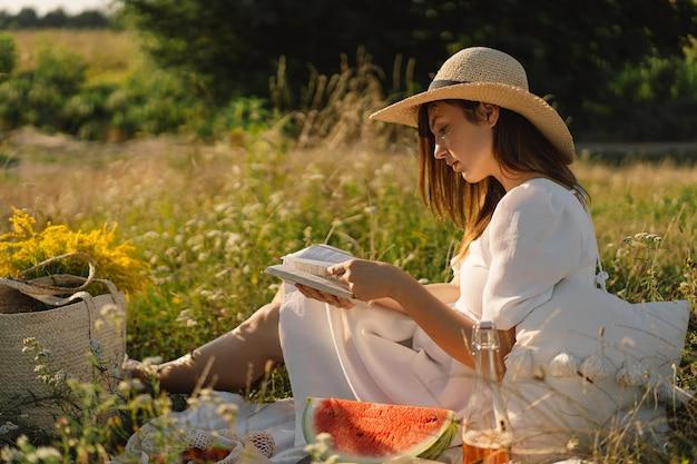 Jonge vrouw leesboek in openlucht veld lezen en ontspanning