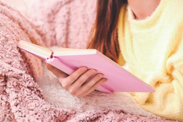 Jonge vrouw leesboek thuis, close-up