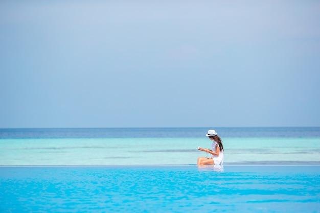 Jonge vrouw leesboek tijdens tropisch wit strand