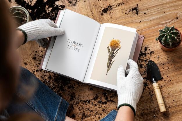 Jonge vrouw leest een boek over tuinieren