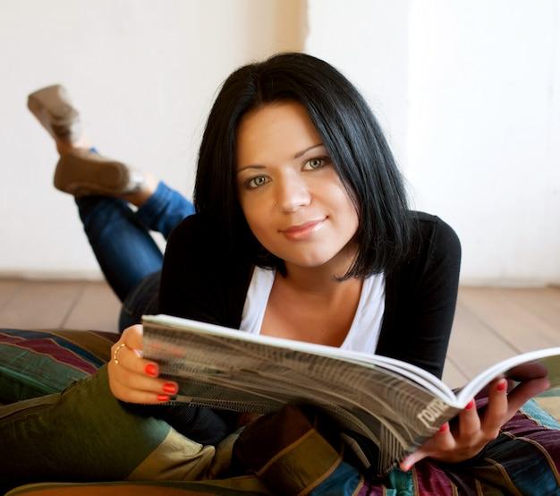 Jonge vrouw leest het tijdschrift