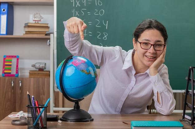 Jonge vrouw leraar bril houden globe wijzend met wijsvinger naar het glimlachend vrolijk uitleggen les zit op schoolbank voor schoolbord in klas