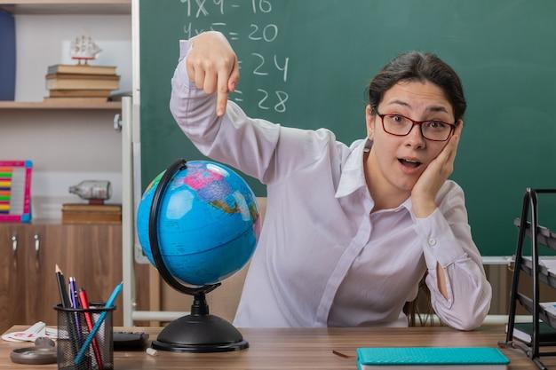 Jonge vrouw leraar bril houden globe wijzend met wijsvinger naar het uitleggen les glimlachend vrolijk op zoek verrast zit op schoolbank voor schoolbord in klas