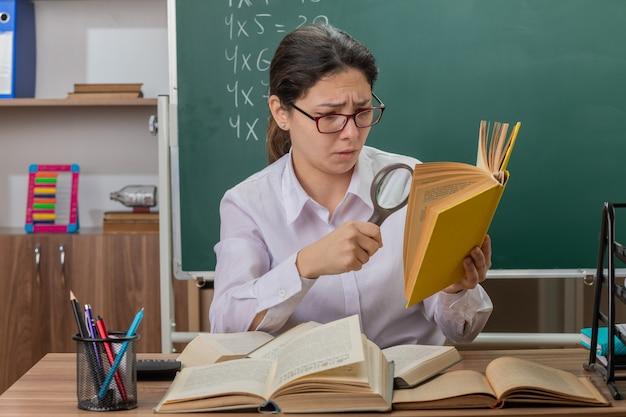 Jonge vrouw leraar bril kijken boek door vergrootglas wordt verward en ontevreden zit op schoolbank voor schoolbord in klas