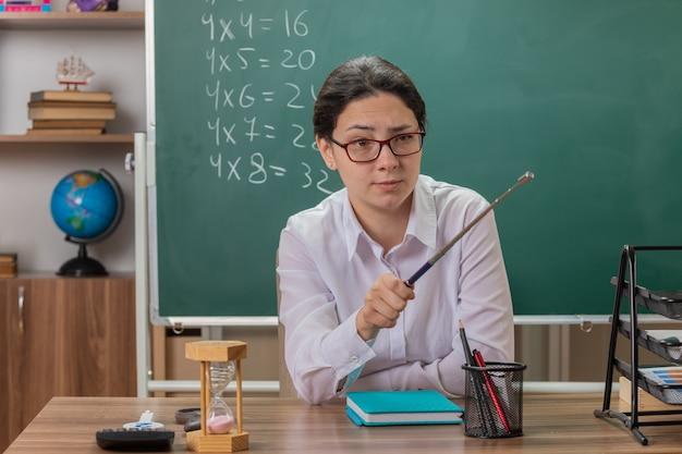 Jonge vrouw leraar bril kijken opzij met ernstig gezicht wijzend met aanwijzer op iets uitleggen les zit op schoolbank voor schoolbord in klas
