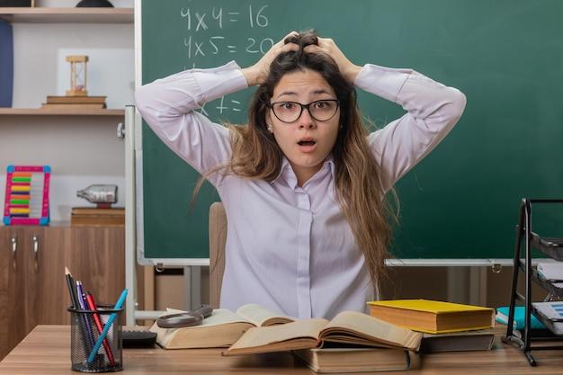 Jonge vrouw leraar bril met boeken op zoek verward en bezorgd met handen op haar hoofd zit op schoolbank voor schoolbord in de klas