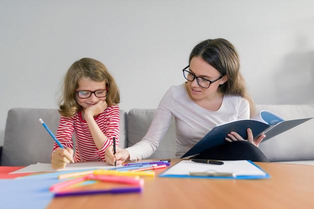 Jonge vrouw leraar onderwijst basisschool meisje