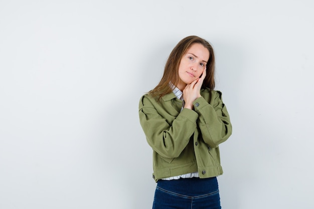 Jonge vrouw leunend op handpalmen als kussen in shirt en ziet er mooi uit. vooraanzicht.