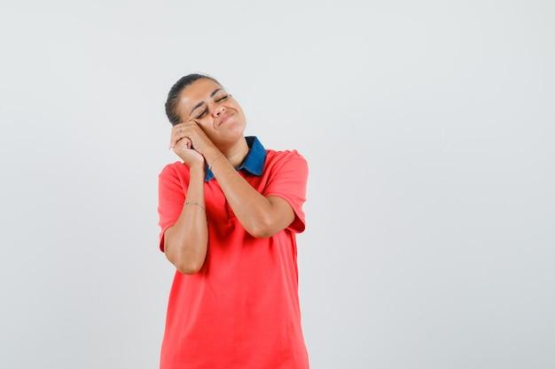 Jonge vrouw leunend wang op handen, probeert te slapen in rood t-shirt en slaperig op zoek. vooraanzicht.