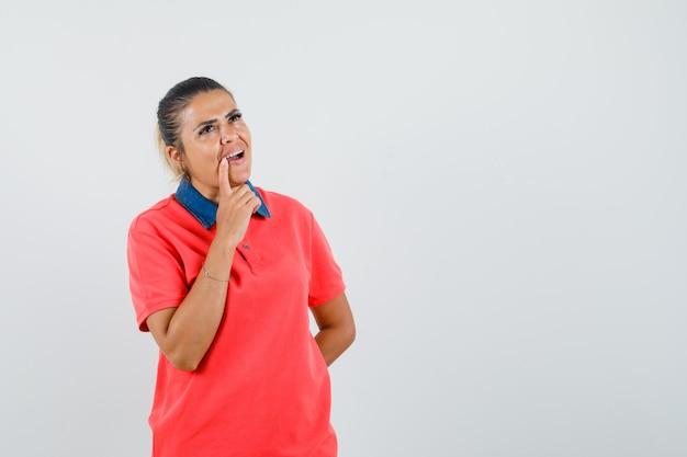 Jonge vrouw leunende vinger in de buurt van mond, staande in denken pose in rood t-shirt en peinzend op zoek. vooraanzicht. Gratis Foto