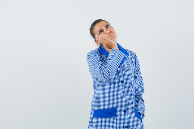 Jonge vrouw leunende wang op handpalm, staande in het denken gebaar in het blauwe overhemd van de gingangpyjama en op zoek peinzend, vooraanzicht.