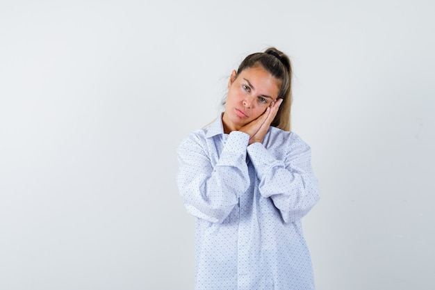 Jonge vrouw leunende wang op handpalmen als kussen in wit overhemd en op zoek slaperig