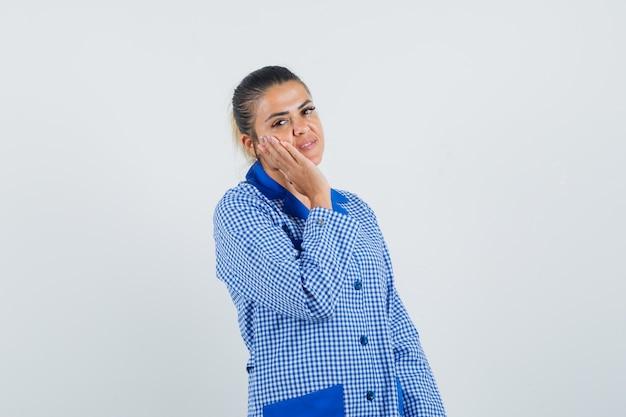 Jonge vrouw leunende wang op palm in het blauwe overhemd van de gingangpyjama en ziet er mooi uit. vooraanzicht.