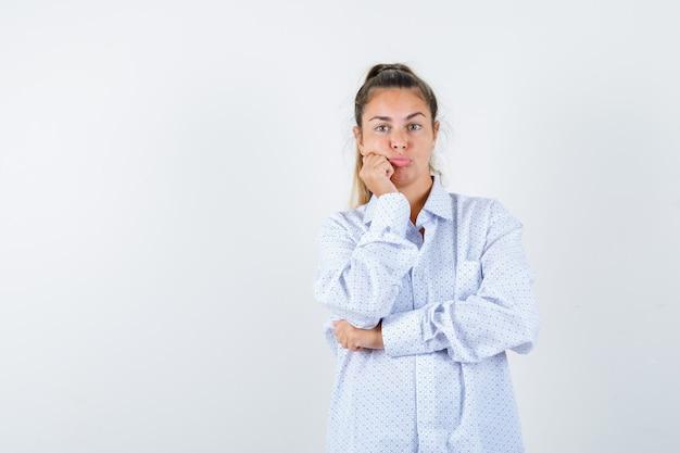 Jonge vrouw leunende wang op vuist, gebogen lippen in wit overhemd en op zoek teleurgesteld