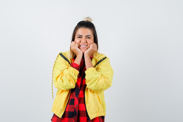 Jonge vrouw leunt kin op haar handen in geruit hemd, jasje en ziet er vrolijk uit. vooraanzicht.