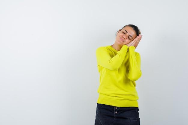 Jonge vrouw leunt wang op handen in trui, spijkerrok en ziet er slaperig uit