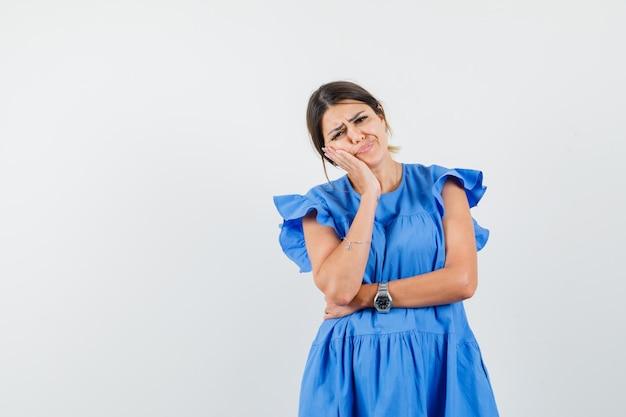 Jonge vrouw leunt wang op opgeheven handpalm in blauwe jurk en ziet er somber uit