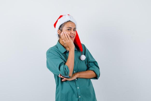 Jonge vrouw leunt wang op opgeheven handpalm in shirt, kerstmuts en schaamt zich. vooraanzicht.