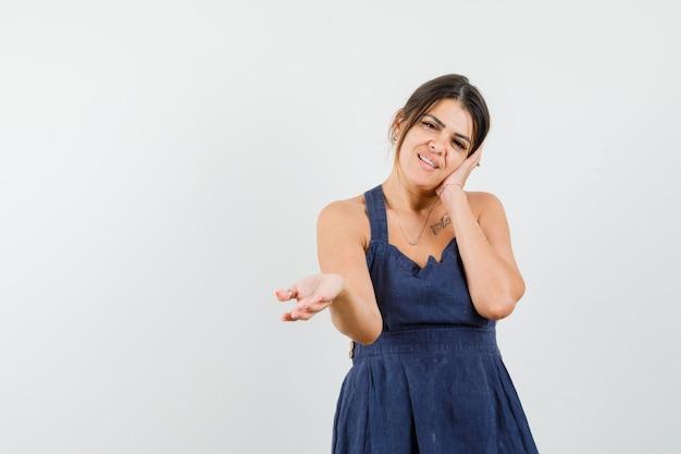 Jonge vrouw leunt wang op palm, strekt hand uit in donkerblauwe jurk en kijkt verward