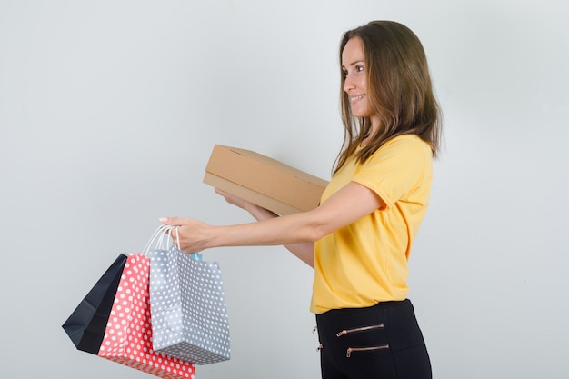 Jonge vrouw levert papieren zakken met kartonnen doos in geel t-shirt, broek en kijkt blij. .