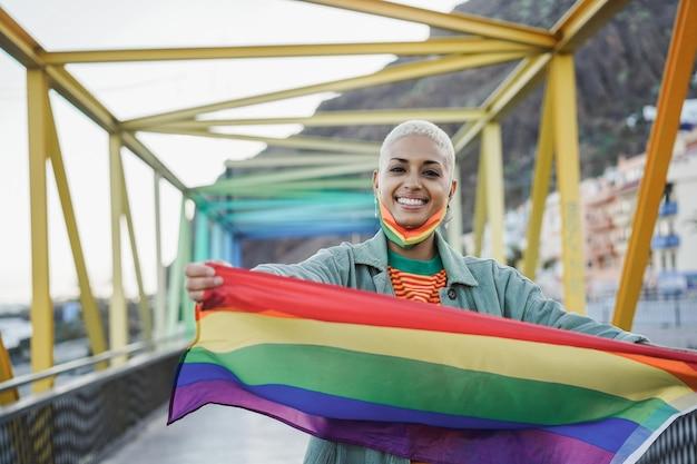 Jonge vrouw lgbt regenboogvlag buiten tijdens uitbraak van coronavirus - focus op gezicht